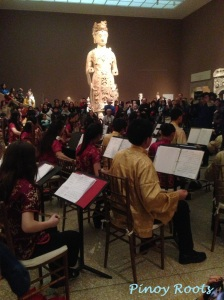 Chinese music performed by a youth orchestra surrounded by ancient art
