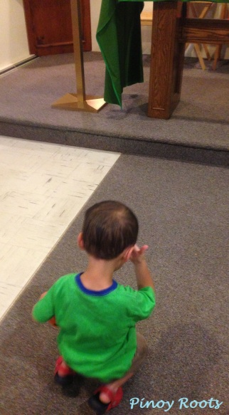 A 2-yr old genuflecting (kneeling) and crossing himself in church